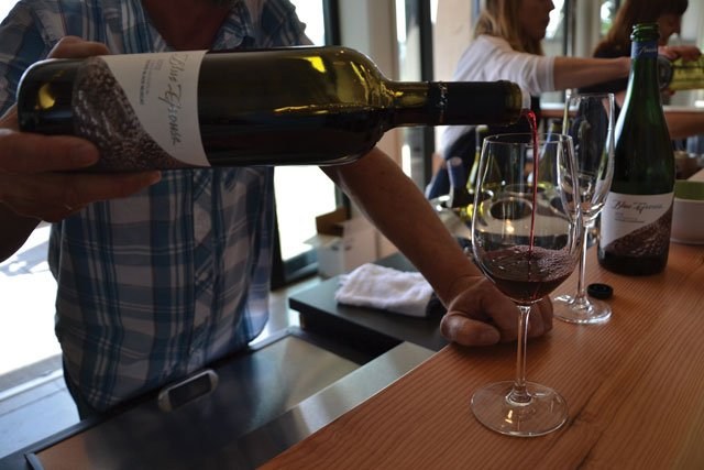 Pouring wine in the Blue Grouse tasting room.